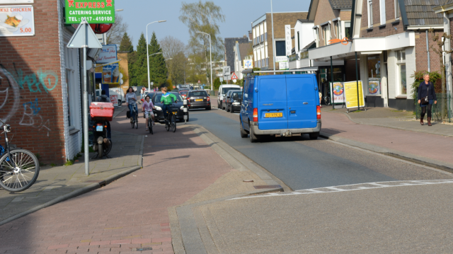 Vehicles queuing, while people cycling have uninterrupted progress