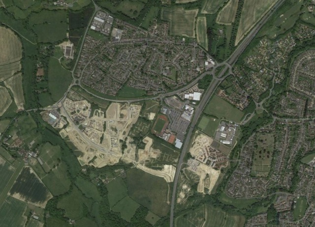 The yellow areas are the new (greenfield) development, approximately doubling the size of the village above it.