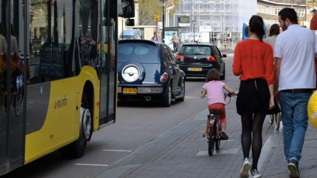 A young child cycling beside a bus, in Utrecht.