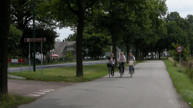 Cycling three abreast on the service road, parallel to the fast main road.