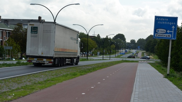 A road for motor vehicles, with a road for cycles alongside it.