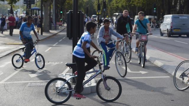 Young asian kids cycling from the centre of London to Tower Hamlets on new cycling infrastructure